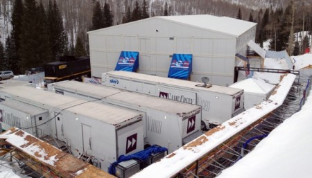 The broadcast compound; TV trucks in the foreground, temporary 3-story building in the background