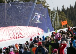A downhill racer flies above the crowd