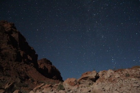 A starry sky over moonlit rocks