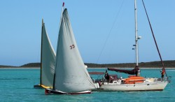 Racers pass an anchored cruising boat
